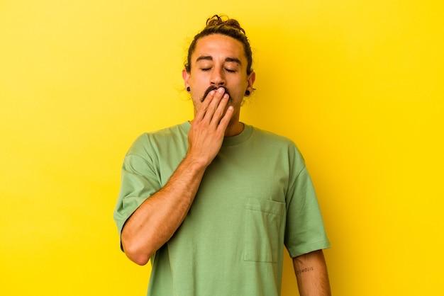 Hombre caucásico joven con pelo largo aislado sobre fondo amarillo bostezando mostrando un gesto cansado cubriendo la boca con la mano.