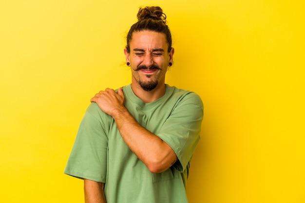 Hombre caucásico joven con el pelo largo aislado sobre fondo amarillo con dolor en el hombro.