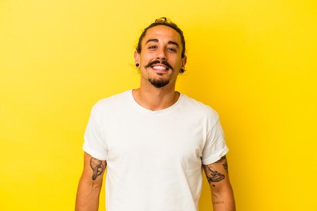 Hombre caucásico joven con pelo largo aislado sobre fondo amarillo feliz, sonriente y alegre.