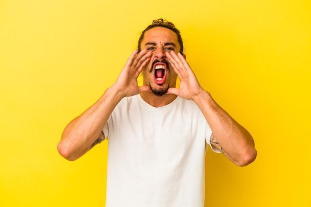 Hombre caucásico joven con el pelo largo aislado sobre fondo amarillo gritando emocionado al frente.