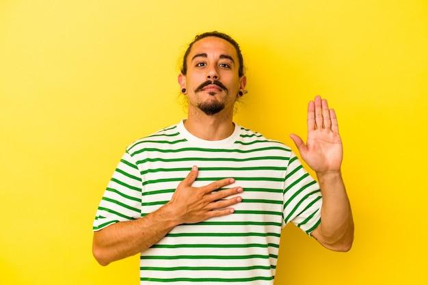 Hombre caucásico joven con el pelo largo aislado sobre fondo amarillo haciendo un juramento, poniendo la mano en el pecho.