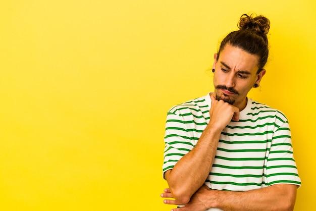 Hombre caucásico joven con pelo largo aislado sobre fondo amarillo mirando hacia los lados con expresión dudosa y escéptica.