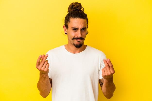 Hombre caucásico joven con pelo largo aislado sobre fondo amarillo mostrando que no tiene dinero.