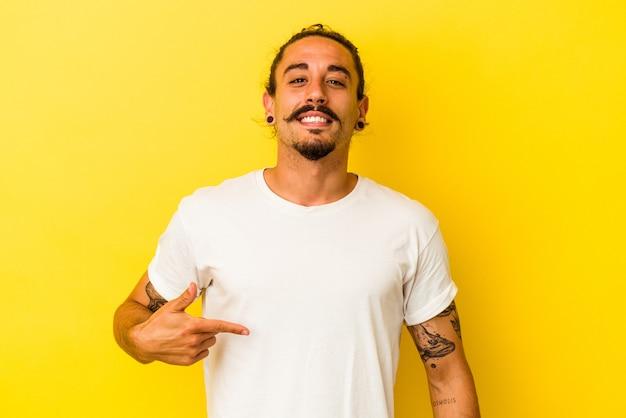 Hombre caucásico joven con pelo largo aislado sobre fondo amarillo persona apuntando con la mano a un espacio de copia de camisa, orgulloso y seguro