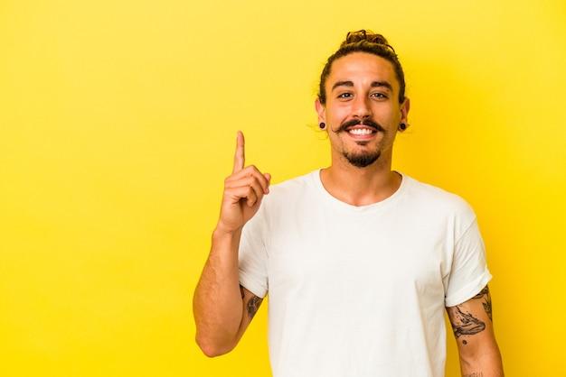 Hombre caucásico joven con el pelo largo aislado sobre fondo amarillo que muestra el número uno con el dedo.