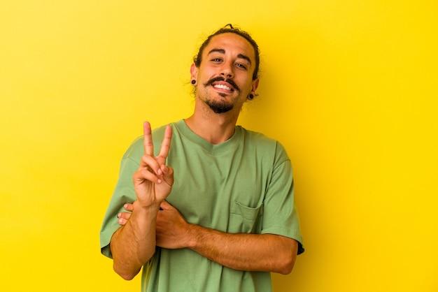 Hombre caucásico joven con el pelo largo aislado sobre fondo amarillo que muestra el número dos con los dedos.