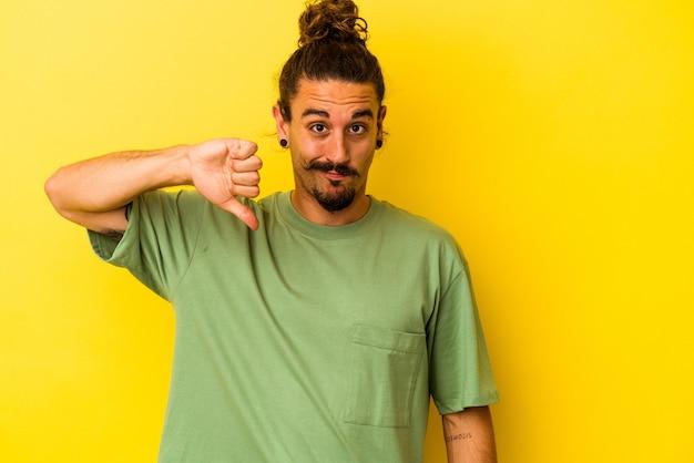 Hombre caucásico joven con el pelo largo aislado sobre fondo amarillo que muestra el pulgar hacia abajo, concepto de decepción.