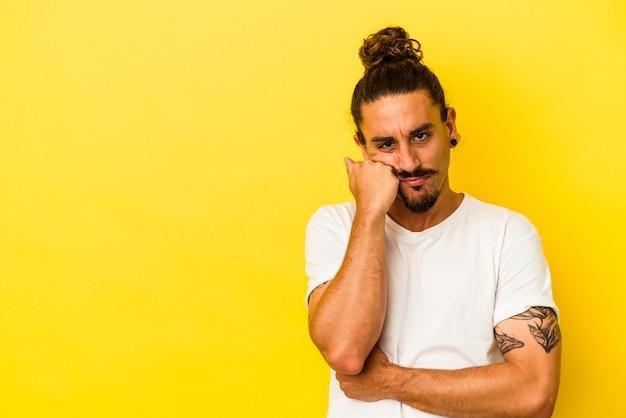 Hombre caucásico joven con pelo largo aislado sobre fondo amarillo que se siente triste y pensativo, mirando el espacio de la copia.
