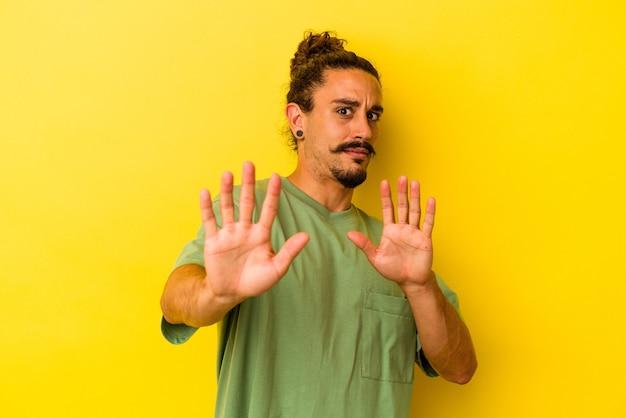 Hombre caucásico joven con pelo largo aislado sobre fondo amarillo rechazando a alguien mostrando un gesto de disgusto.