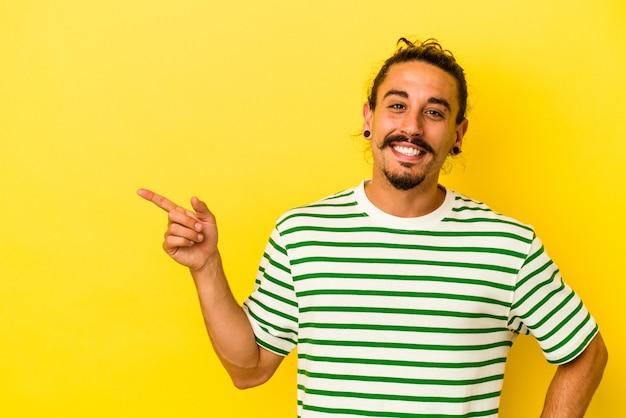 Hombre caucásico joven con pelo largo aislado sobre fondo amarillo sonriendo alegremente apuntando con el dedo índice.