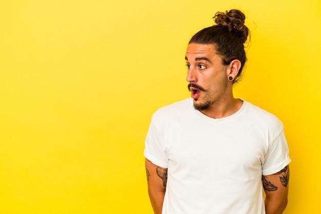 Hombre caucásico joven con pelo largo aislado sobre fondo amarillo sorprendido por algo que ha visto.
