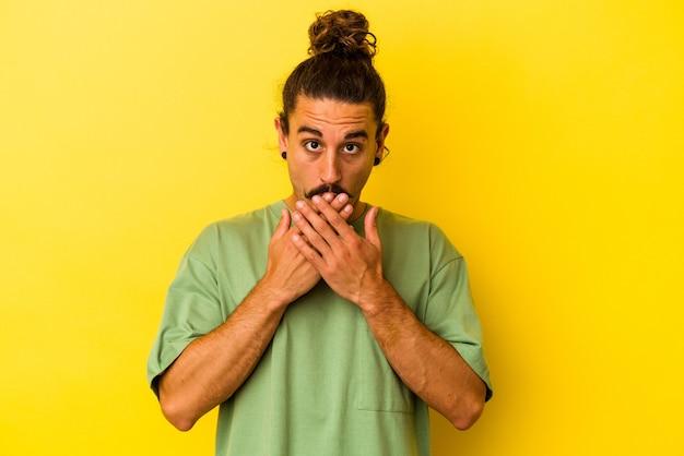 Hombre caucásico joven con el pelo largo aislado sobre fondo amarillo sorprendido cubriendo la boca con las manos.