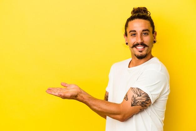 Hombre caucásico joven con pelo largo aislado sobre fondo amarillo sosteniendo un espacio de copia en una palma.