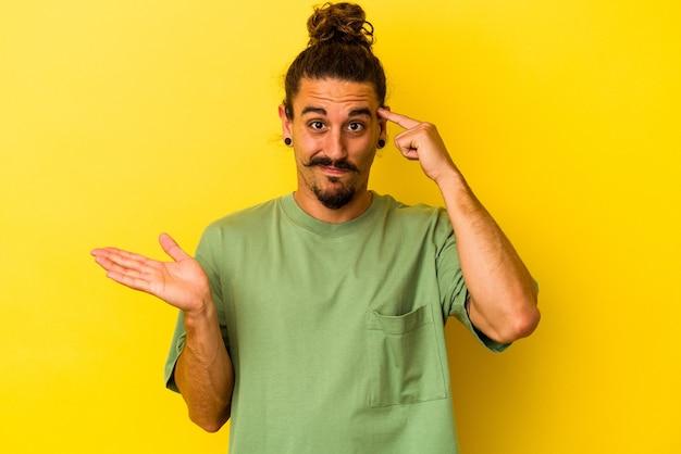 Hombre caucásico joven con pelo largo aislado sobre fondo amarillo sosteniendo y mostrando un producto en la mano.