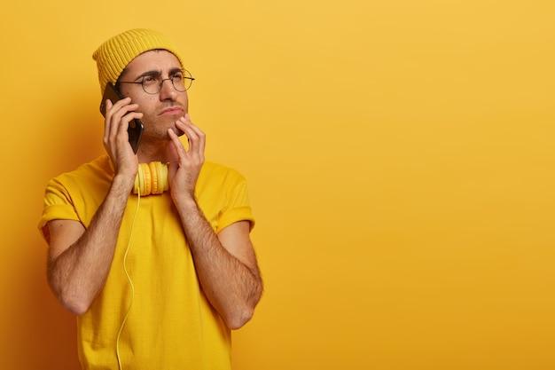 Hombre caucásico joven pensativo serio se da la vuelta, piensa en algo profundamente, usa gafas transparentes, camiseta amarilla casual y tocados