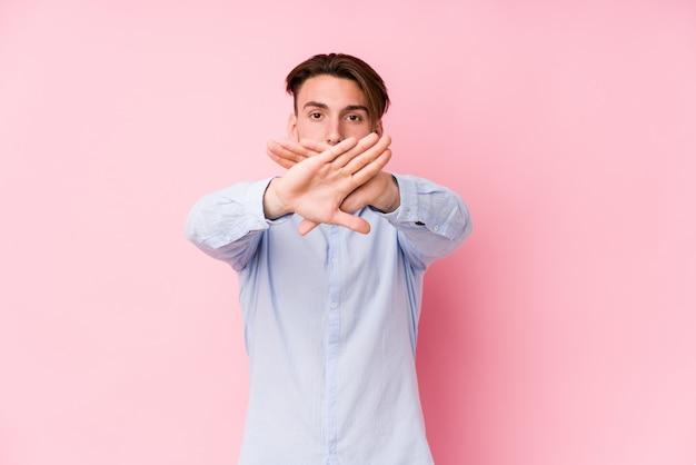 Hombre caucásico joven posando en un fondo rosa aislado haciendo un gesto de negación