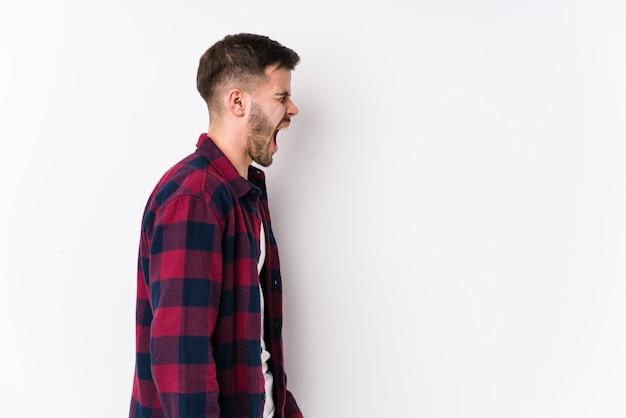 Hombre caucásico joven posando en una pared blanca gritando hacia un espacio en blanco