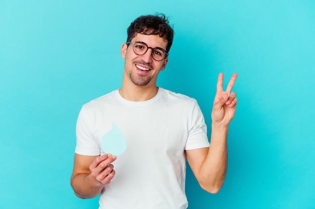 Hombre caucásico joven que celebra el día mundial del agua aislado alegre y despreocupado mostrando un símbolo de paz con los dedos.
