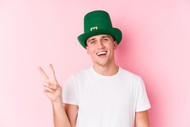 Hombre caucásico joven que celebra el día de san patricio alegre y despreocupado que muestra un símbolo de paz con los dedos.