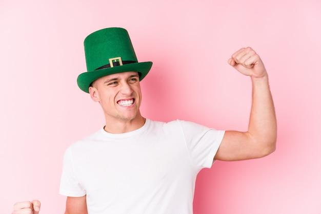 Hombre caucásico joven que celebra el día de san patricio que levanta el puño después de una victoria, concepto del ganador.