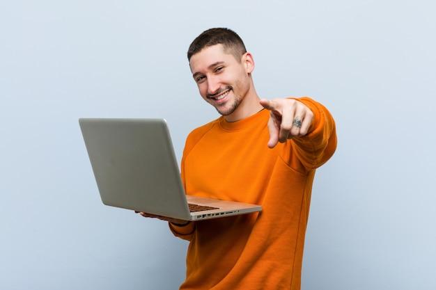 Hombre caucásico joven que celebra sonrisas alegres de una computadora portátil que señalan al frente.