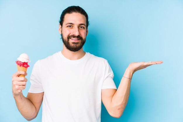 Hombre caucásico joven que come un helado aislado que muestra un espacio de la copia en una palma y que lleva a cabo otra mano en la cintura.