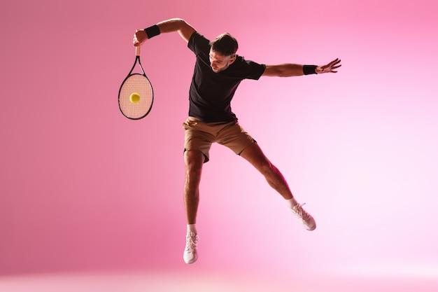 Hombre caucásico joven que juega al tenis aislado en la acción de la pared rosada y el concepto del movimiento
