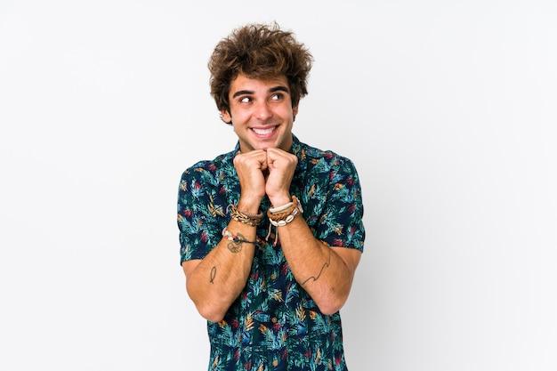 El hombre caucásico joven que lleva una camiseta de la flor aislada mantiene las manos debajo de la barbilla, está mirando felizmente a un lado.