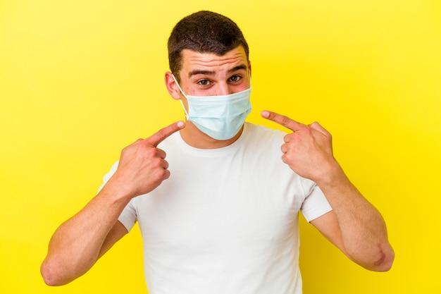 Hombre caucásico joven que lleva una protección para el coronavirus aislado en la pared amarilla sonríe, señalando con el dedo a la boca
