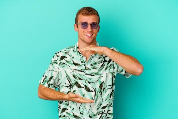 Hombre caucásico joven que lleva una ropa de verano aislada en azul que sostiene algo con ambas manos, presentación del producto.