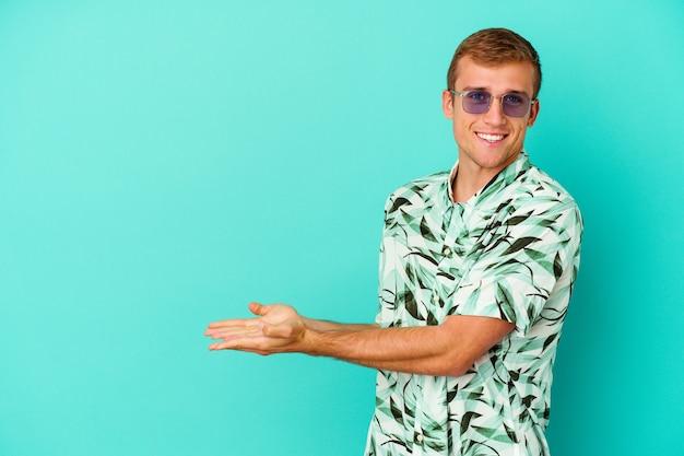 Hombre caucásico joven que lleva una ropa de verano aislada en azul que sostiene un espacio de la copia en una palma.