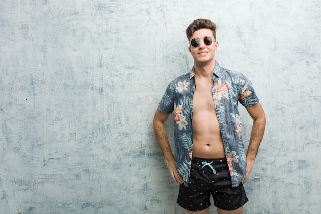 Hombre caucásico joven que lleva un traje de baño confiado que mantiene las manos en él caderas.