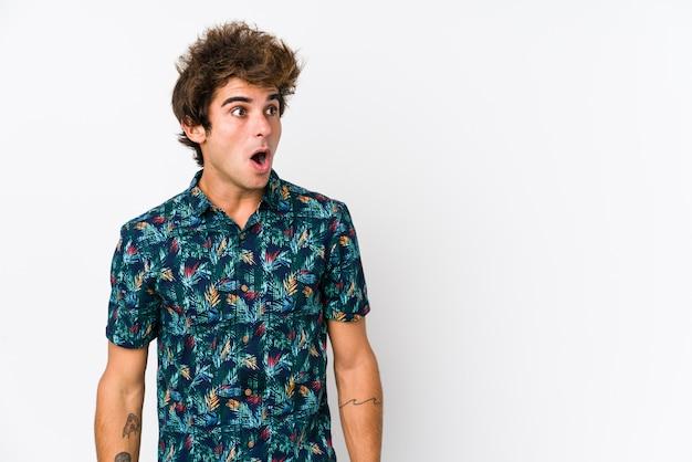 Hombre caucásico joven que llevaba una camiseta de flores aislado ser sorprendido por algo que ella ha visto.