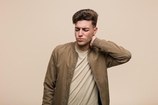 Hombre caucásico joven que llevaba una chaqueta marrón que sufría dolor de cuello debido al estilo de vida sedentario.