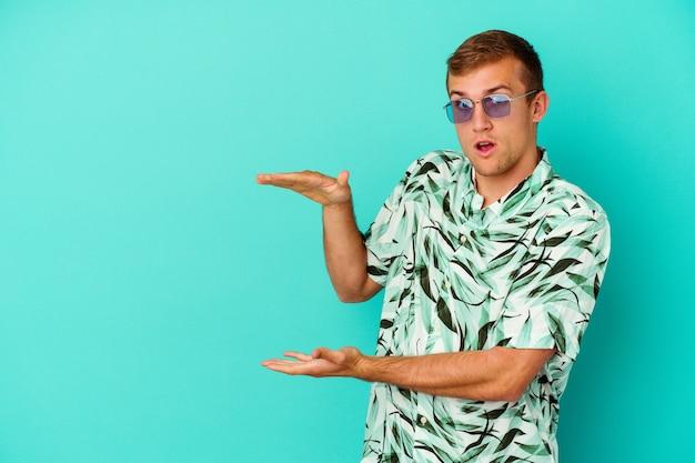 Hombre caucásico joven que llevaba una ropa de verano aislada en la pared azul conmocionado y sorprendido sosteniendo un espacio de copia entre las manos.