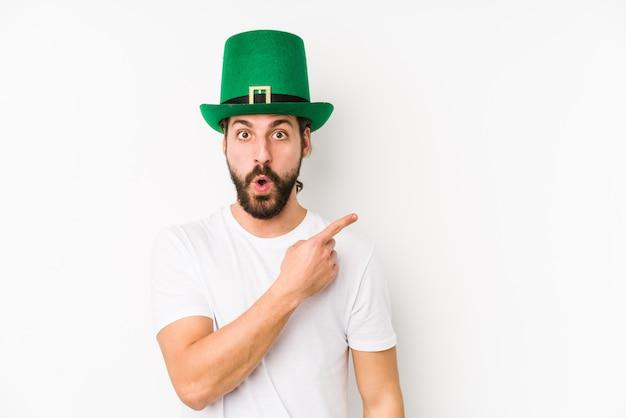 Hombre caucásico joven que llevaba un sombrero de san patricio aislado apuntando hacia el lado