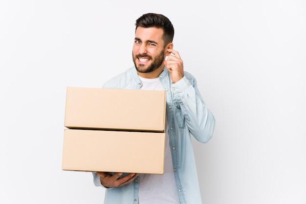 Hombre caucásico joven que se muda a un nuevo hogar aislado cubriendo los oídos con las manos.