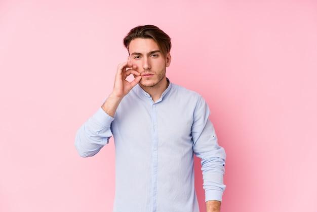 Hombre caucásico joven que presenta en una pared rosada aislada con los dedos en los labios que guardan un secreto.