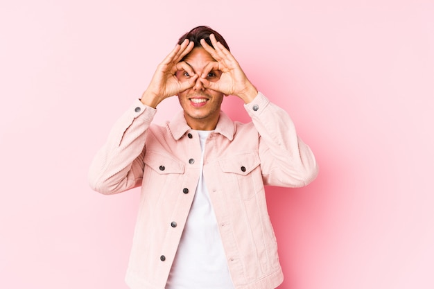 Hombre caucásico joven que presenta en una pared rosada aislada que muestra la muestra aceptable sobre ojos
