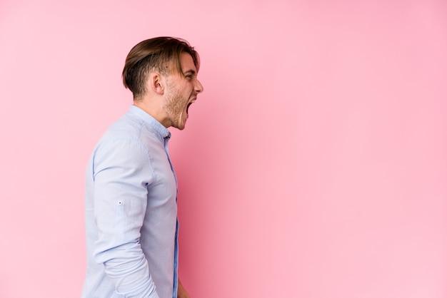 Hombre caucásico joven que presenta en una pared rosada que grita hacia un espacio en blanco
