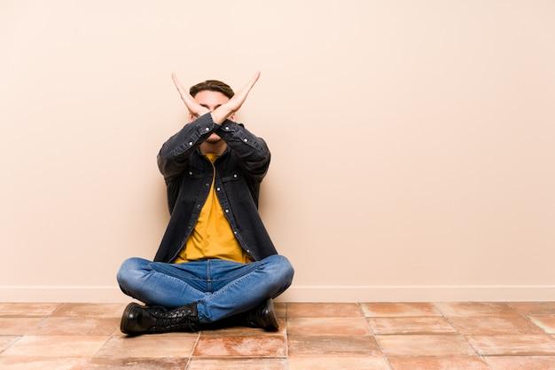Hombre caucásico joven que se sienta en el piso aislado manteniendo dos brazos cruzados, concepto de la negación.