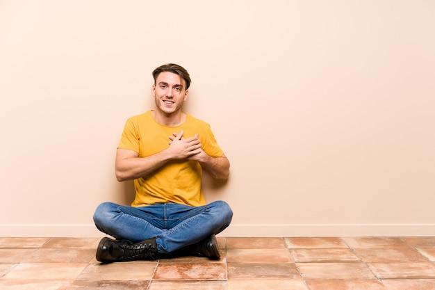 El hombre caucásico joven que se sienta en el piso aislado tiene expresión amistosa, presionando la palma al pecho. concepto de amor