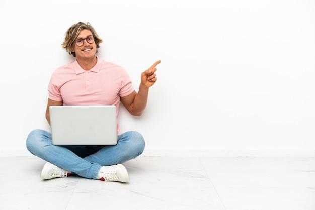 Hombre caucásico joven que se sienta en el suelo con su computadora portátil aislada en blanco que señala el dedo hacia el lado