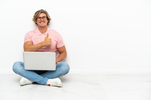 Hombre caucásico joven que se sienta en el suelo con su computadora portátil aislada en la pared blanca que da un gesto del pulgar hacia arriba