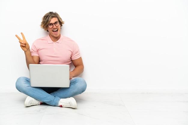 Hombre caucásico joven que se sienta en el suelo con su computadora portátil aislada en la pared blanca que sonríe y que muestra el signo de la victoria