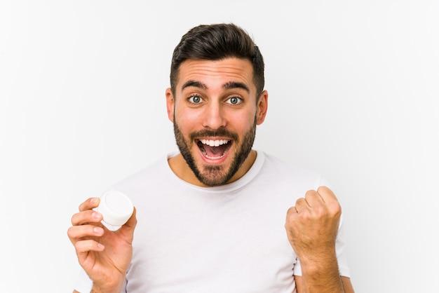 El hombre caucásico joven que sostenía una crema hidratante aisló animar despreocupado y emocionado. concepto de victoria