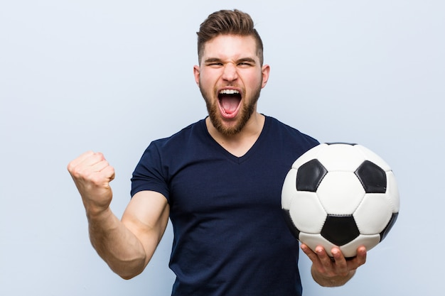 Hombre caucásico joven que sostiene un balón de fútbol que anima despreocupado y emocionado.