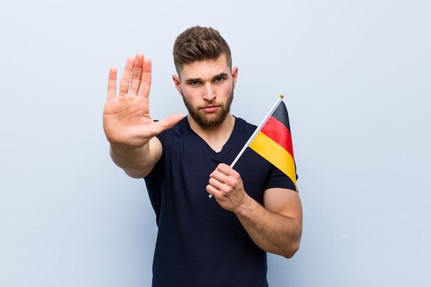 Hombre caucásico joven que sostiene una bandera de alemania que se coloca con la mano extendida que muestra la señal de stop, previniéndole.