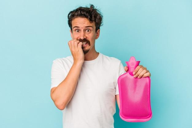 Hombre caucásico joven que sostiene una bolsa de agua aislada sobre fondo azul mordiéndose las uñas, nervioso y muy ansioso.