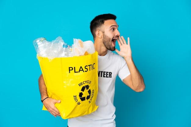 Hombre caucásico joven que sostiene una bolsa llena de botellas de plástico para reciclar aislado en la pared azul gritando con la boca abierta hacia un lado